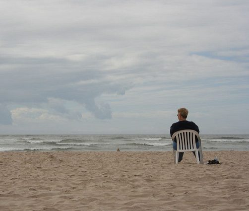 man sitting alone in chair on beach