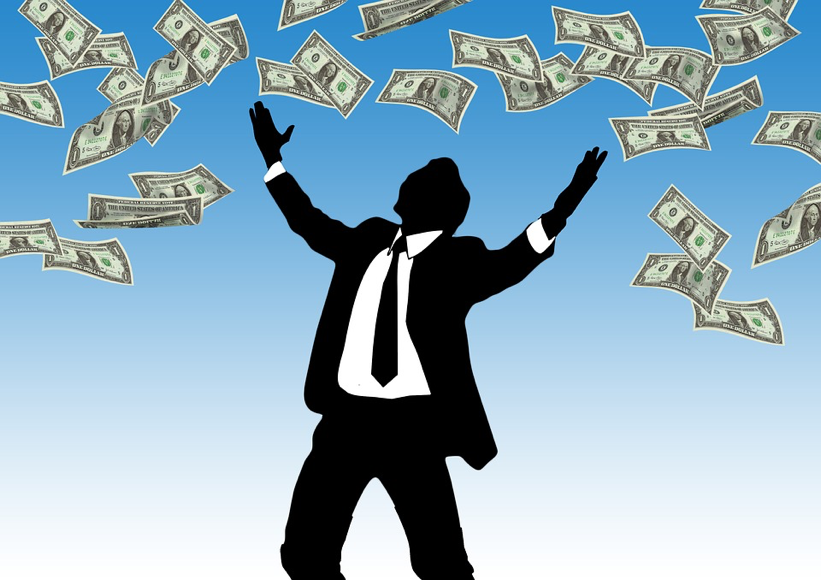 businessman with cash raining down on him