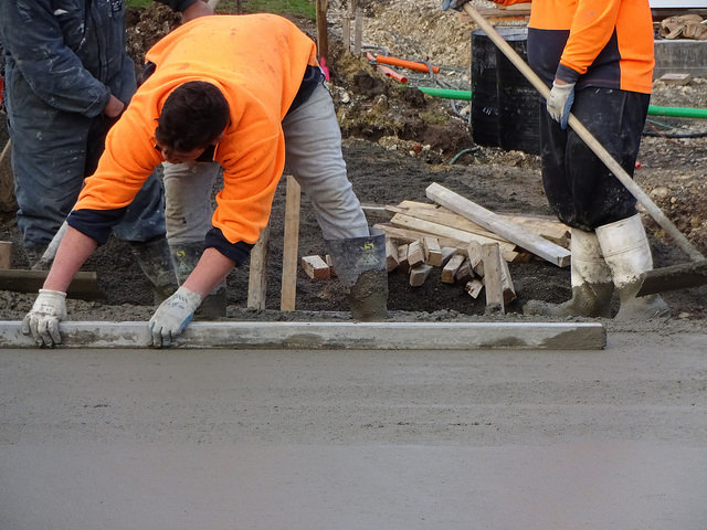 man pouring a concrete patio